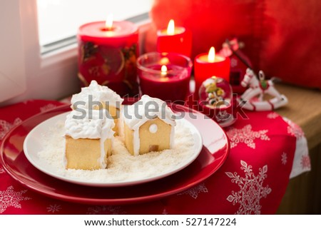 Christmas decoration: gingerbread houses, candies, toys and burning red candles on windowsill