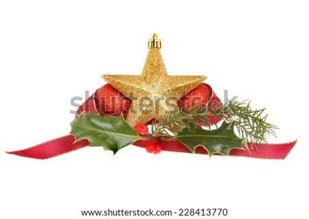 Christmas decoration, gold star with red baubles, pine needles, holly and a red ribbon isolated against white - stock photo