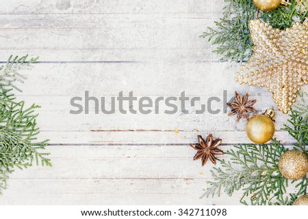 Christmas decoration. Golden balls, star, anise and fir tree branches on the white snowy wooden background. - stock photo