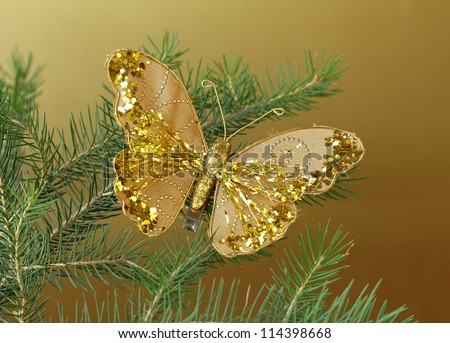 Christmas decoration (golden butterfly) on the branches of fir - stock photo