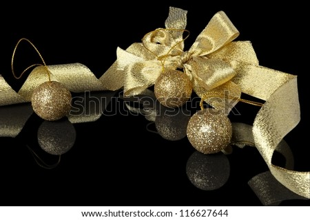 Christmas decoration - golden ribbon with bow isolated on black - stock photo