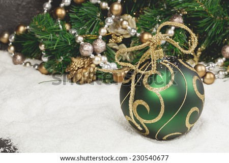 Christmas decoration. Green Christmas Balls Ornaments and Christmas Tree on a snowy background. Macro, selective focus. Done with a vintage retro filter