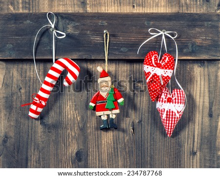 christmas decoration handmade toys hanging over rustic wooden background. nostalgic retro style toned picture - stock photo