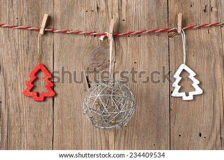 Christmas decoration hanging on clothesline on old wooden background
