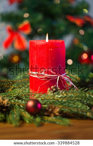 christmas, decoration, holidays and advertisement concept - close up of natural green fir branch wreath with red burning candle on wooden board - stock photo