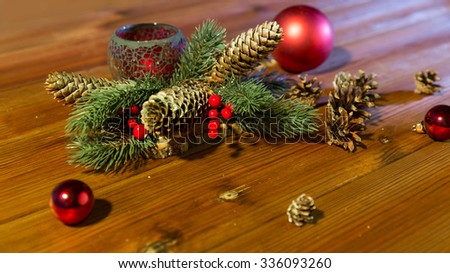 christmas, decoration, holidays and new year concept - close up of natural fir branch decoration with fir-cones, balls and candle in lantern on wooden table - stock photo