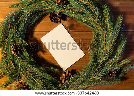 christmas, decoration, holidays, greeting and advertisement concept - close up of natural green fir branch wreath with white blank paper sheet on wooden board - stock photo