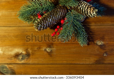 christmas decoration, holidays, new year and decor concept - close up of natural fir branch and fir-cone on wooden table - stock photo