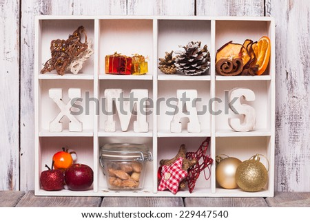 Christmas decoration in a wooden box. Cozy holiday in home. Wood letters XMAS in shadow box memories - stock photo