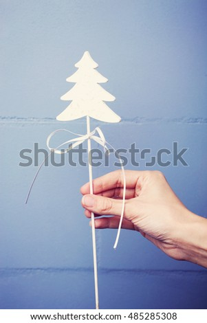 Christmas decoration in hand  with a wall in a background. Vintage colors