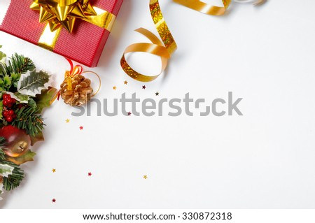 Christmas decoration isolated white on the left. Red and gift box and golden ribbon with floral ornament. Top view. Horizontal and diagonal composition. - stock photo