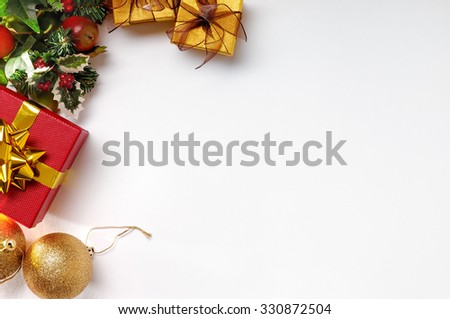 Christmas decoration isolated white on the left. Red and golden gift boxes with golden ball, and floral ornament. Top view. Horizontal composition. - stock photo