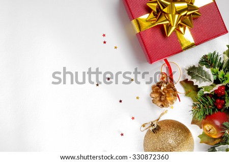 Christmas decoration isolated white on the right. Red gift box with golden ball, and floral ornament. Top view. Horizontal composition. - stock photo