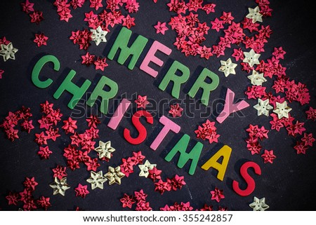 Christmas decoration items are spread on black background. Empty space for writing on the board.