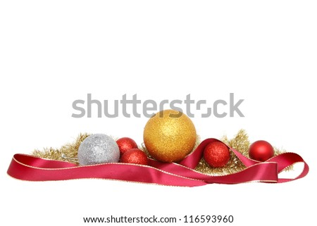 Christmas decoration of baubles tinsel and gold edged red ribbon isolated against white - stock photo
