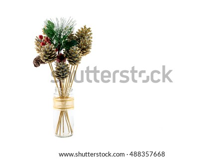 Christmas decoration of gold painted fir cones, red berries and Holly in glass jar isolated on white
