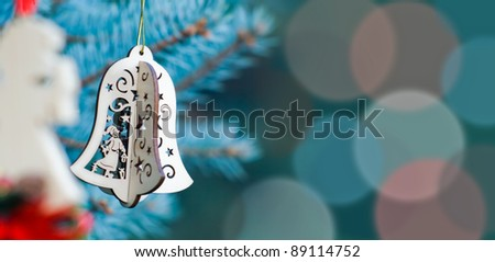 Christmas decoration of woody angel and handmade bell on the blue background of fir-tree having much space for text - stock photo