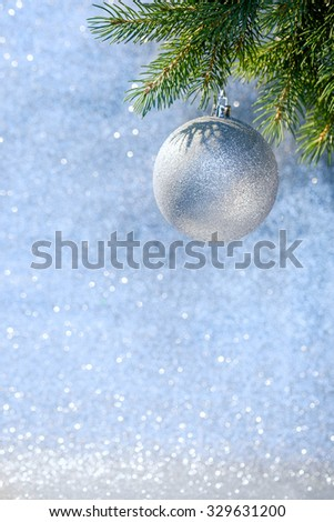 Christmas decoration on a Christmas tree branch over blurred shiny background. Space for text.