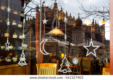Christmas decoration on the cafe window in Krakow. In the glass display Cloth Hall in the town square.