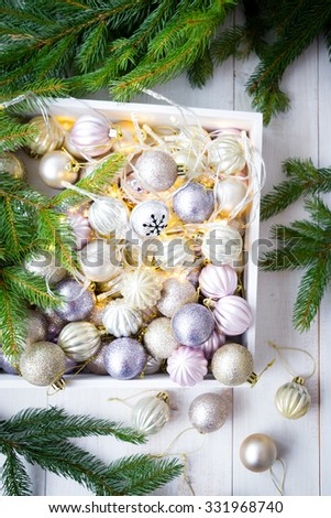 christmas decoration, ornaments in a wooden box, pine branches, christmas lights
