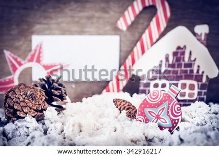Christmas decoration over grunge background/ vintage handmade christmas decoration and snow on wooden background with copy space, ginger bread cookie house, candy cane, red star and christmas ball