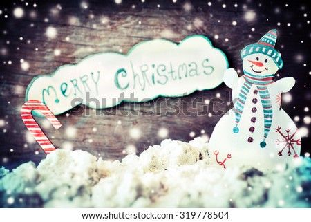 Christmas decoration over grunge background/vintage paper handmade christmas decoration and snow on wooden background with copy space, Merry christmas letters and Snowman - stock photo