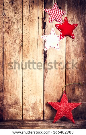 Christmas decoration over wooden background. Vintage Christmas Card with festive stars hanging on wood wall. Rustic Christmas Ornaments with copy space.
