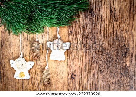 Christmas decoration - pine twigs, earthen crafts on wooden background. Space for text - stock photo
