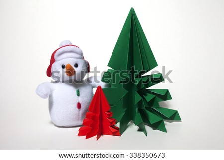 Christmas decoration, plush snowman with origami trees isolated on white background