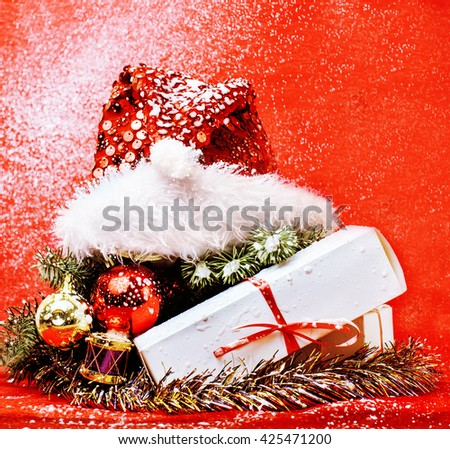 christmas decoration , red background with snow for post card greetings, toy design on tree macro xmas gifts under santas hat - stock photo
