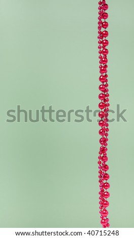 Christmas decoration red beads on green background with empty place for your text