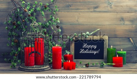 christmas decoration red candles and pine branch. nostalgic home interior with blackboard on wooden background. sample text Happy Holidays! - stock photo