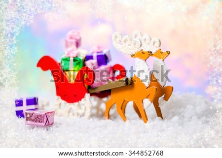 Christmas decoration reindeer and Santa sleigh with gifts in snow on north polar light background, closeup - stock photo