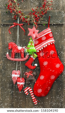 christmas decoration santa's sock and handmade toys over rustic wooden background. nostalgic retro style picture with falling snow effect
