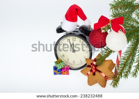 Christmas decoration - table clock, gingerbread, candy cane, colorful gifts, balls and fir branches on a white background - stock photo