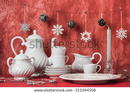 Christmas decoration table display in simple and elegant style. White crockery over red background - stock photo