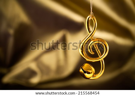 Christmas decoration, treble clef jingle bell on silky gold/green background.  - stock photo