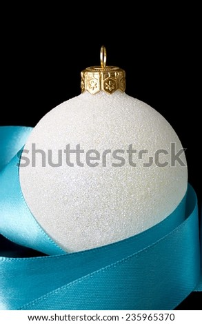 Christmas decoration  white ball with ribbon on black background - stock photo