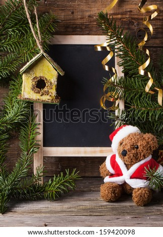 Christmas decoration with antique teddy bear in santa`s hat with blank slate and nesting box over wooden background - stock photo