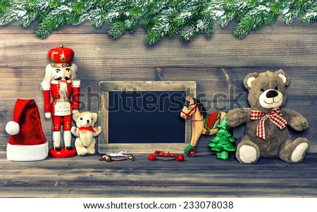 christmas decoration with antique toys, pine tree branches and blackboard for your text. retro style toned picture - stock photo