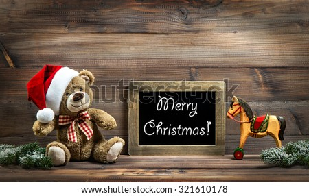 Christmas decoration with antique toys teddy bear and wooden rocking horse. Vintage style picture with blackboard. Sample text Merry Christmas! - stock photo
