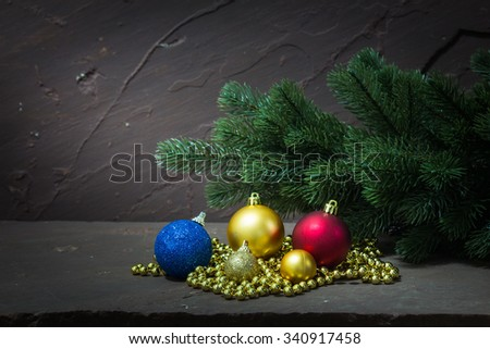 Christmas decoration with bauble and fir on brown stone table over stone grunge background - stock photo