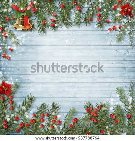 Christmas decoration with bell and holly on a wooden background