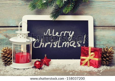 Christmas  decoration with candle in lantern and framed blackboard on wooden background - stock photo