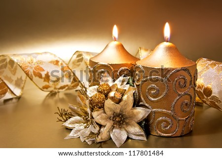 Christmas decoration with candles and ribbon over golden background - stock photo
