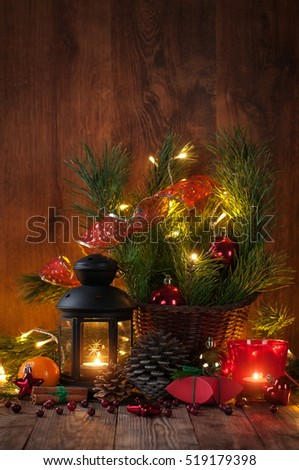 Christmas decoration with candles, lantern, pine branches, pine cones, balls garland, gift on wooden background