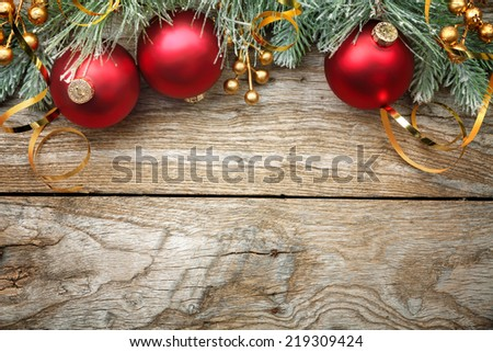 Christmas decoration with fir and baubles over wooden background. - stock photo