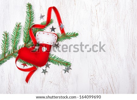 Christmas decoration with fir branch, red ribbon and sock - stock photo