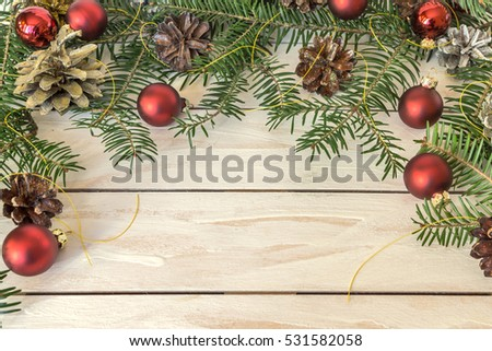 Christmas decoration with fir branches, cones and toys on white wooden background