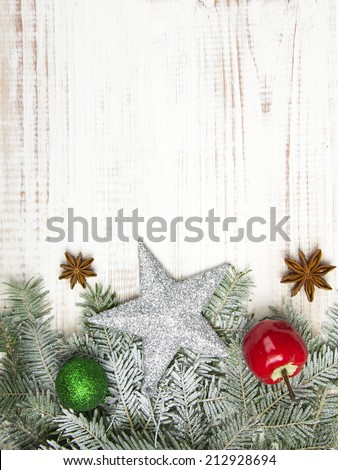 Christmas decoration with fir twigs, baubles, silver star and artificial snow with a blank space